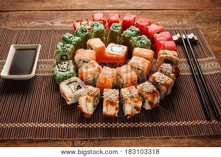 Colorful japanese sushi, food art. Appetizing colorful spiral of delicious uramaki rolls set served on brown straw mat, closeup. Oriental luxury restaurant menu photo.