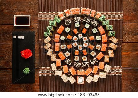 Food art, great sushi set. Appetizing assortment of rolls, colorful round ornament served on brown straw mat, flat lay. Luxury japanese restaurant menu photo.