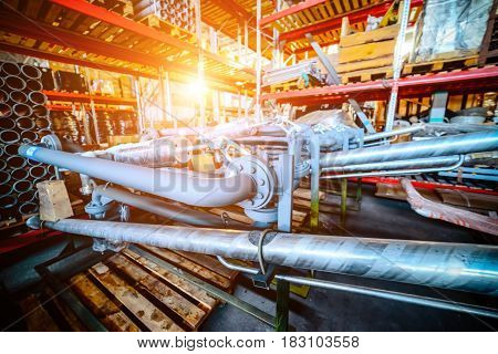 Industrial Warehouse. Various mechanisms and gray metal pipe. Toning the image. Bright sunlight.