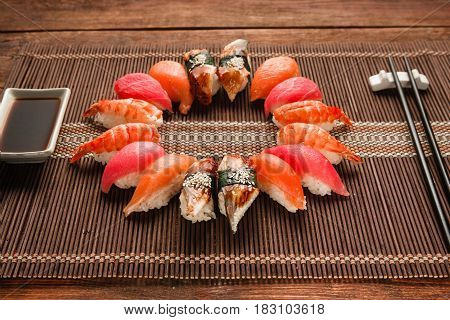 Colorful japanese sushi set, seafood. Great assortment of nigiri nigiri served like circle on brown straw mat, close up. National seafood, restaurant menu photo.