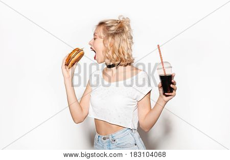 Pretty woman with a glass of fizzy water biting a burger. Horizontal studio shot.