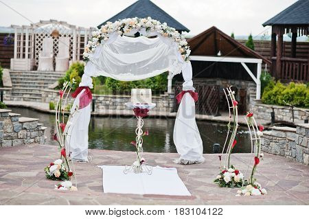 Decor wedding arch with red ribbon at ceremony outdoor.