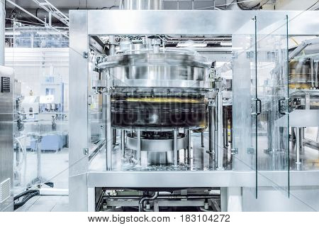 The filling machine pours beer into plastic PET bottles. Brewing production, abstract industrial background. Toning the image.