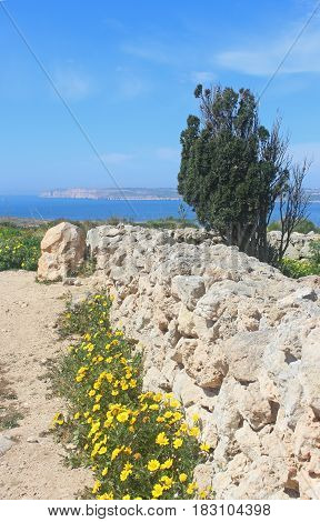 Mediterranean scene: view from Malta to Gozo with a natural stone wall in the foreground