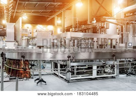 The filling machine pours beer into plastic PET bottles. Brewing production, abstract industrial background.
