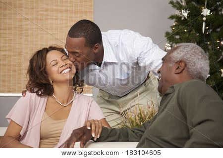 Man kissing woman near Christmas tree