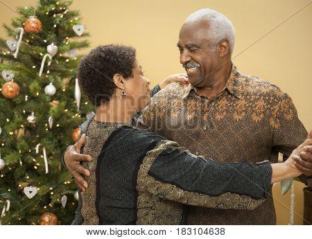 African couple dancing near Christmas tree