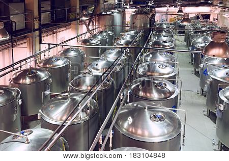 Industrial shop with a lot of metal tanks, built in long rows. Modern brewing production.