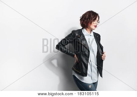Beautiful young female in black leather coat and glasses posing on white background.