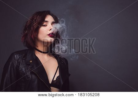 Young sexy girl in bra and leather jacket breathing out smoke on dark background.