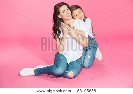 Happy Beautiful Mother And Daughter Sitting Together And Hugging On Pink