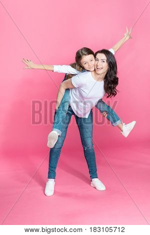 Happy Mother Piggybacking Adorable Little Daughter With Open Arms On Pink