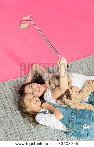 High Angle View Of Happy Mother And Daughter Lying Together And Taking Selfie