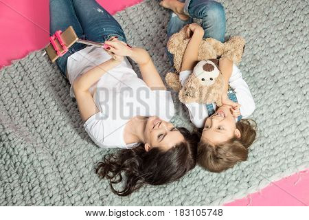Elevated View Of Happy Mother And Daughter Lying Together And Taking Selfie