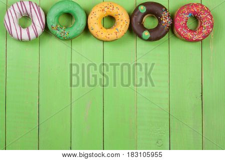 glazed donuts on a green wooden background with copy space for your text. Top view.