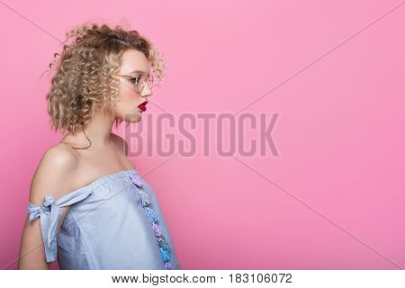 Young stylish girl in glasses posing on pink background.