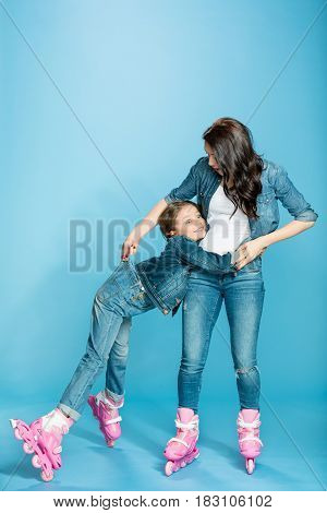 mother and daughter in roller skates hugging in studio on blue