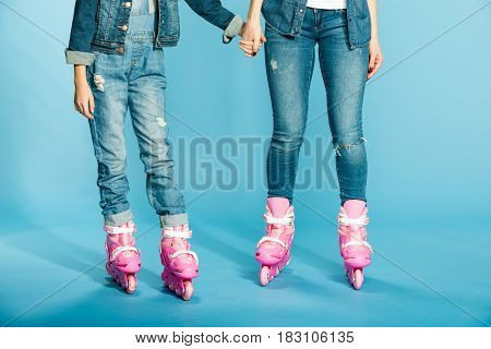 Mother And Daughter In Roller Skates Holding Hands In Studio On Blue