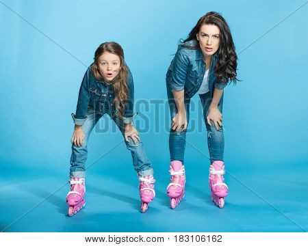 Tired Mother And Daughter In Roller Skates In Studio On Blue