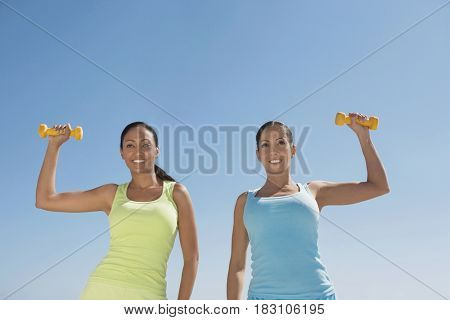 Hispanic women exercising with dumbbells