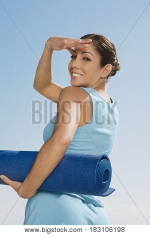 Hispanic woman holding yoga mat