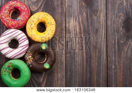 glazed donuts on a black wooden background with copy space for your text. Top view.