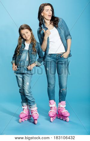 Mother And Daughter In Roller Skates, Woman With Thumb Up In Studio On Blue