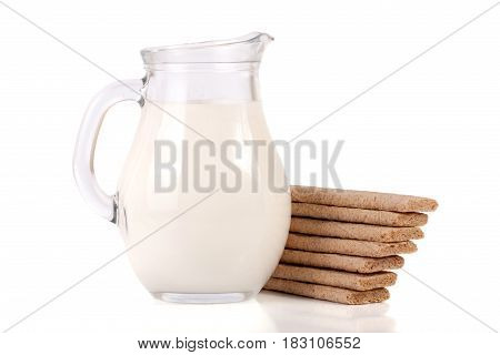 jug of milk with stack of grain crispbreads isolated on white background.