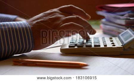 Accountant Using Calculator With Paperwork.
