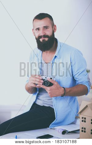 Handsome young man holding digital camera on white background