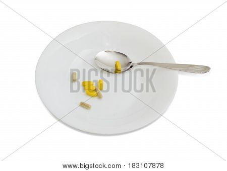 Multivitamins in the form of tablets and dietary supplements in the form of capsules on the white dish and spoon on a light background