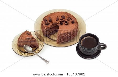 Partly sliced chocolate cake decorated with chocolate chips and cocoa powder on the glass dish slice cake on saucer with spoon and black coffee in black ceramic cup on a light background