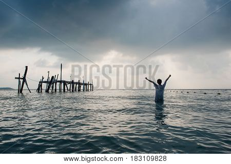 Women in the sea with open arms . Happy freedom for success and bliss concept.