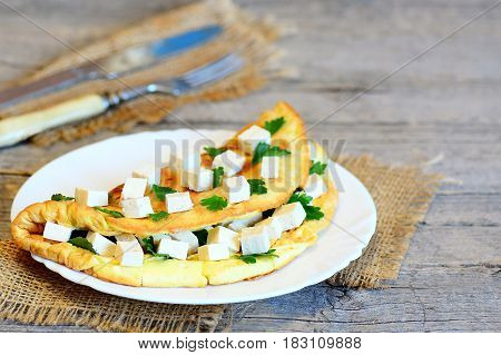 Homemade egg omelette stuffed with tofu cubes and fresh parsley on a wooden board. Fork, knife, burlap textile on rustic wooden table. Healthy breakfast omelette for whole family. Closeup