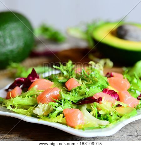 Salmon, avocado and lettuce salad on a plate. Diet salad with slices of smoked salmon, fresh avocado and lettuce leaves mix. Avocado fruit and half on a wooden table. Closeup