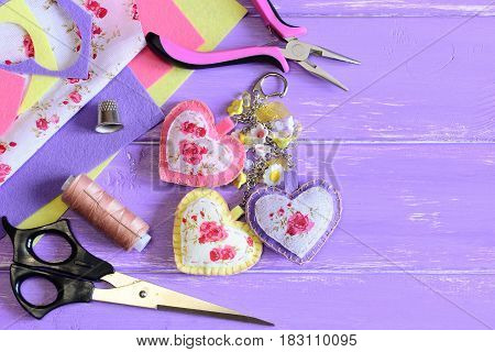 Cute hearts keyring. Homemade felt and fabric keyring or bag charm. Scissors, pliers, felt, needle, thread, scrap, fabric on wooden background with copy space. Set to create beautiful crafts. Top view