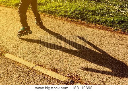 Boy riding roller blades on the street. Young unrecognizable child enjoying childhood outdoor sport activity on his roller-skates
