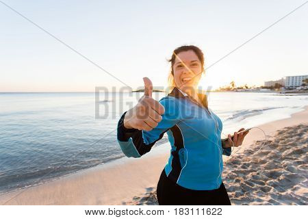 Smiling female fitness show thumbs up and holding smartphone with earphones. Outdoor sport, fitness gadget and people concept.