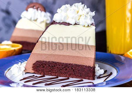 slice of cake mousse three chocolates on blue plate