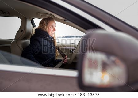 Woman driving a car - female driver at a wheel of a modern car (shallow DOF; color toned image)