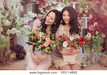 Beautiful asian florist girls making bouquet of flowers on table for sale against floral bokeh background in flower shop indoors. Two attractive asian females florists working in store. 2 playful fashion models in tender dresses smiling and looking at cam