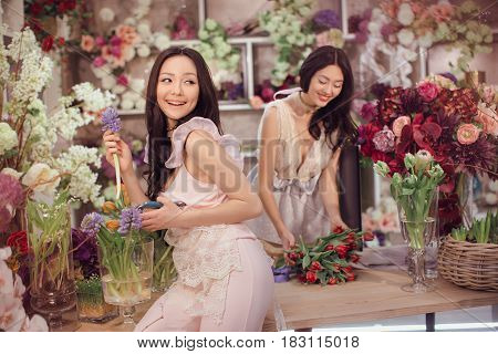 Beautiful asian florist girls making bouquet of flowers on table for sale against floral bokeh background in flower shop indoors. Two attractive asian females florists working in store. 2 playful fashion models in tender dresses happy smiling and playing