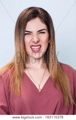 Portrait of angry young woman over blue background