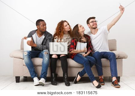Capturing happy moments. Young friends making selfie while sitting together on couch and using gadgets