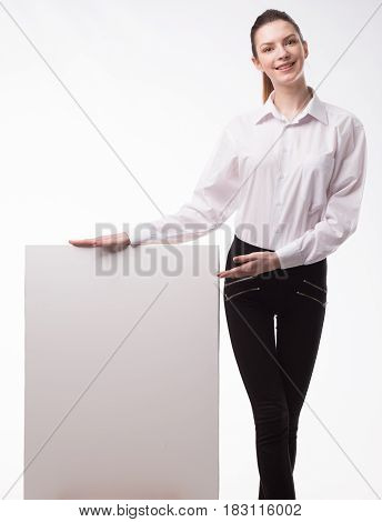 Young happy woman isolated portrait showing presentation, pointing on paper placard. White background. Ideal for banners, registration forms, presentation, landings, presenting concept