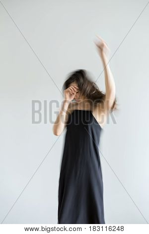 Amazing girl in a dark dress is posing in the motion in the studio on the gray background. She is stretching up her hands. Left hand and hair are blurred. Vertical.