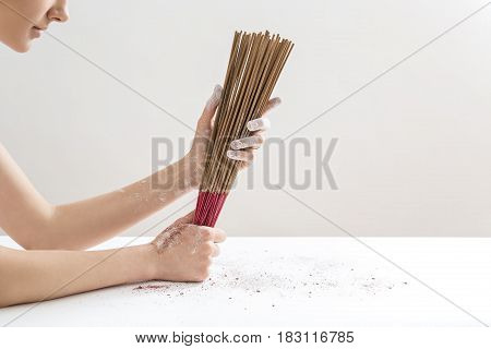 Girl with hands in powder are holding a bunch of incense sticks on the light background in the studio. Sticks colored in red-brown. Closeup. Horizontal.