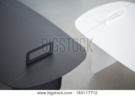 Black and white metal stands on the blurry gray background. Closeup low aperture photo. Indoors. Horizontal.