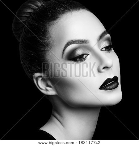 Young woman model with bright makeup, black lips. Over black background