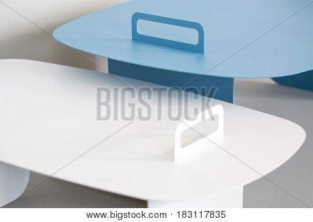 Cyan and white stands on the gray background. Closeup low aperture photo. Indoors. Horizontal.